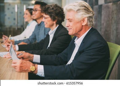 Business people listening to presentation in row