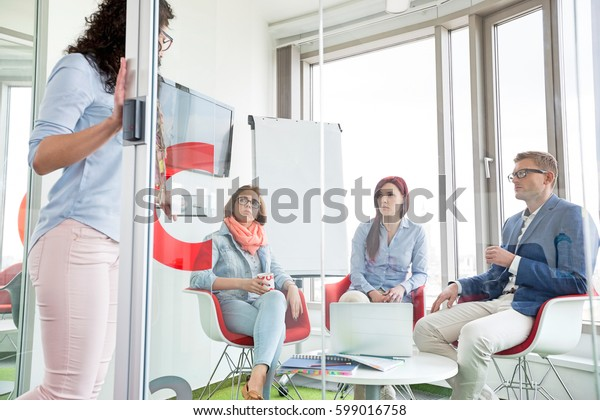 Business people looking at female colleague standing in sliding door