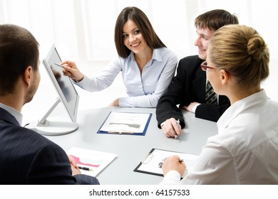 Business people looking at monitir, talking at meeting table in office
