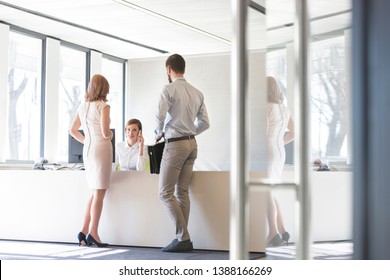 Business people looking at professional talking on phone in office