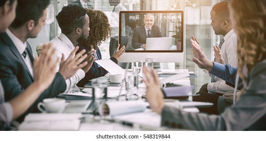 Business people looking at screen during video conference in office