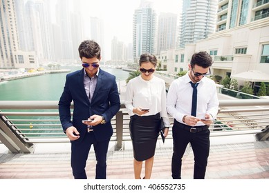 Business people looking at their smart phones.