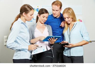 Business people looking together at a tablet computer in the office