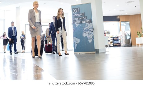 Business people with luggage walking in convention center