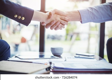 Business people make a deal with handshake at office or cafe. Success business concept.