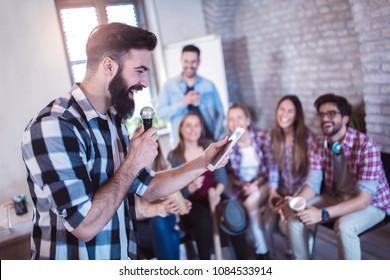 Business people making team training exercise during team building seminar singing karaoke.