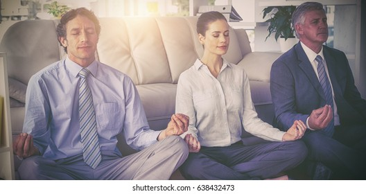 Business people meditating in lotus pose against sofa at office