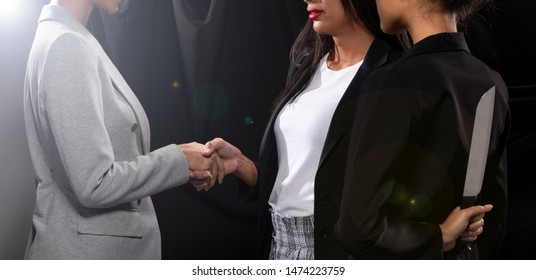 Business people meet and shake hand hello with sincere but one ambitious woman black suit hold and hide knife at the back, ready to betray by stab