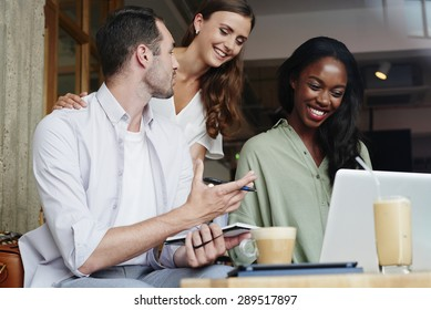 Business people meeting in cafe using laptop drinking coffee