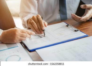 Geschäftsleute treffen sich mit Datendokumenten im Konferenzraum.