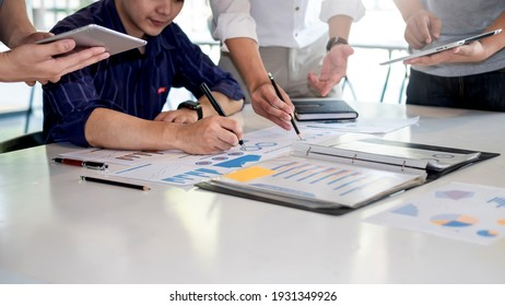 Business people meeting to find analytical ideas pointing to the graph at the office.