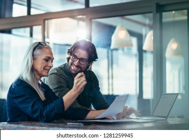 Business people meeting in office and discussing over a documents. Business woman with a financial report in hand sitting with male colleague looking at her and smiling.