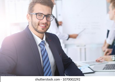 Business people at meeting in office. Focus at cheerful smiling bearded man wearing glasses. Conference, corporate training or brainstorming of people group. Success and negotiation concept