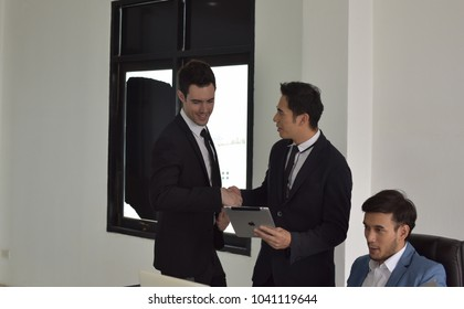 business people in a meeting at office. Portrait of a group of business people working together at a meeting. Business people shaking hands, finishing up a meeting