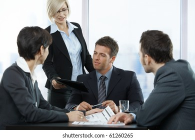 Business people at meeting in office, standing assistant handing over contract to executive sitting with colleagues.?