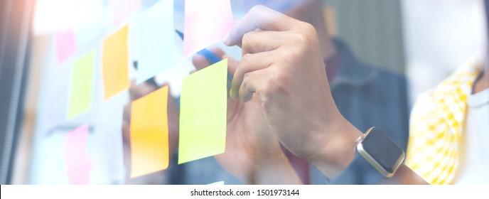 Geschäftsleute, die sich im Büro treffen und klebrige Noten an der Glaswand im Büro verwenden, verschiedene Mitarbeiter, die Planungen zusammenlegen, arbeiten mit Brainstormstrategie zusammen