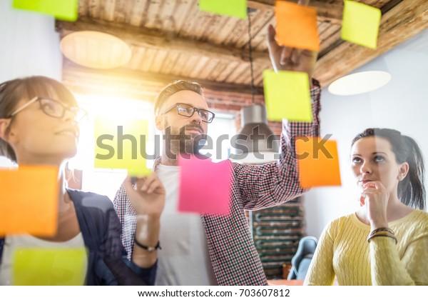Empresarios reunidos en la oficina y usar postes para compartir ideas. Concepto de lluvia de ideas. Nota pegajosa en la pared de vidrio.