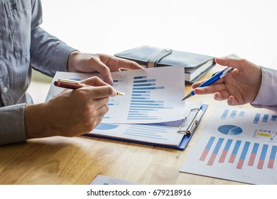 Business people meeting point to discuss, plan and chart the rise and fall of economic on white background.