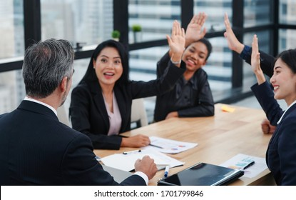 Business people in the meeting room is raised up hands to present the own idea of business planning on how to achieve the business objective. idea, success, brainstorming and collaboration concept.
