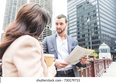 Business people meeting and talking during coffee break in Chicago. Man and woman, wearing smart casual clothes, looking each other and smiling. Downtown skyscrapers on background