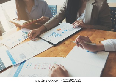 Business People Meeting using laptop computer,calculator,notebook,stock market chart paper for analysis Plans to improve quality next month.