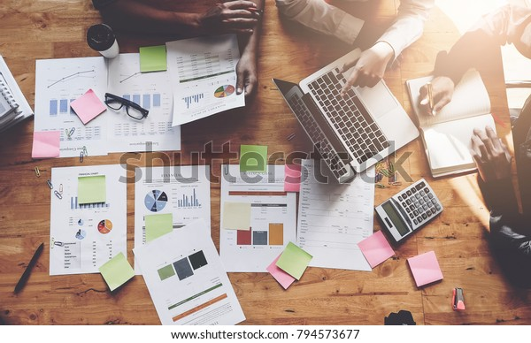 Business People Meeting using laptop computer,calculator,notebook,stock market chart paper for analysis Plans to improve quality next month. Conference Discussion Corporate Concept