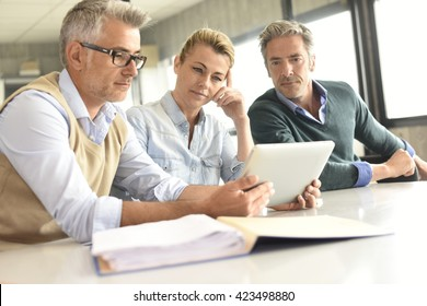Business people in a meeting using tablet