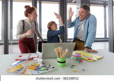 Business people in modern office celebrating good business results.