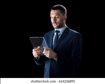 business, people and modern technology concept - businessman in suit working with transparent tablet pc computer over black background