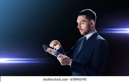 business, people and modern technology concept - businessman in suit working with transparent tablet pc computer over black background and laser light