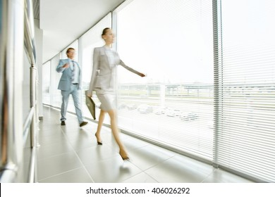 Business people moving along office corridor, blurred motion