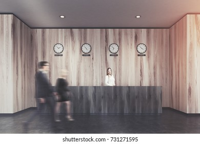 Business people near a wooden reception desk in a modern office with wooden walls and a concrete floor. Clocks showing world time on the wall. 3d rendering mock up toned image