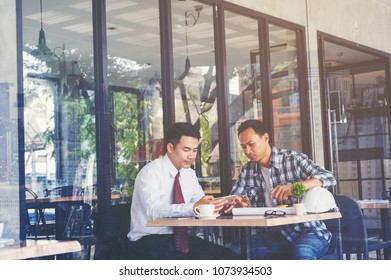 Business people negotiating a contract, they are pointing on a smartphone discussing together. Two businessmen are deal agreement collaboration talk in office concept.