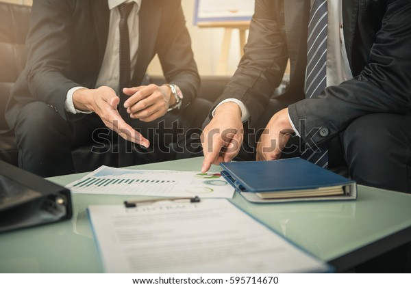 契約交渉を行うビジネスマンは、文書を指し示し、話し合いを進めている。二人の実業家が在職中に交渉を行っている。
