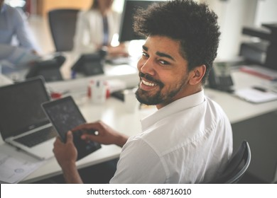 Business people in office. African business man typing on laptop and looking at camera.