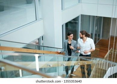 Business People In Office Going To Work. Beautiful Man And Woman Going Up Stairs In Modern Business Center. High Resolution