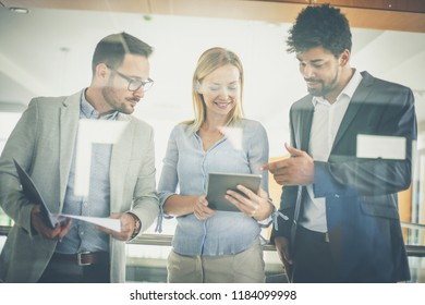 Business people in office having conversation and using digital tablet.