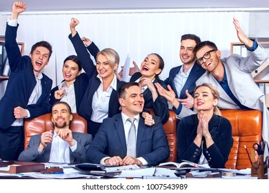 Business people office life of team people are happy with hand up sitting table and working papers . Friday and end of working week. Cabinets with folders and jalousie background.