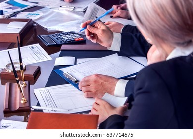 Business people office life of team working with papers sitting table with schemas and diagrams .Cropped shot of body part people wear in suits meeting do work of the accountant and calculate costs.