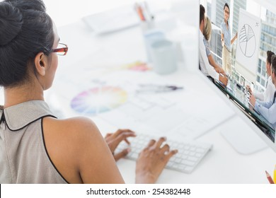Business people in office at presentation against designer working on her computer