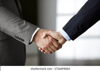 Business people in office suits standing and shaking hands, close-up. Business communication concept. Handshake and marketing