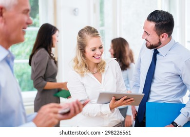 Business people in office working as team, woman showing man presentation on tablet computer