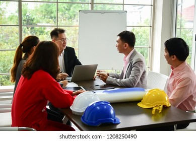 Business people are on discussion in the meeting room with laptop and documents.