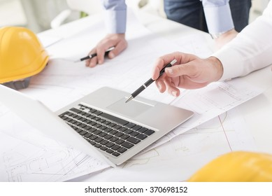 Business people on meeting in bright modern office with blueprint at desk check documents and business workflow on laptop