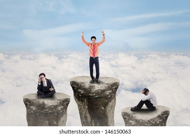 Business people on top of rocks with one winner exulting above clouds