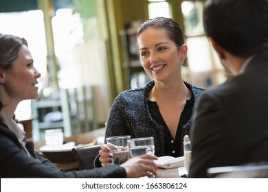Business people outdoors, keeping in touch while on the go. Three people, a man and two women sitting at a table. A meeting or social gathering.
