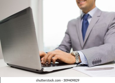 business, people, paperwork and technology concept - close up of smiling businessman with laptop computer and papers working in office