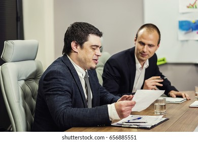 Business people partners discussing in meeting (conference) documents and ideas in a modern office