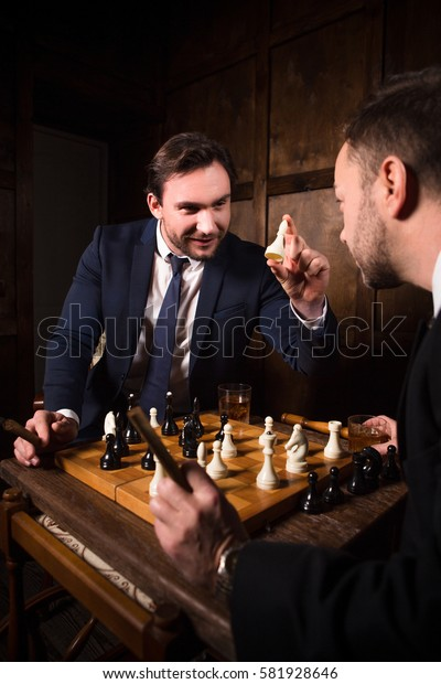 Business people playing chess demonstrating rivalry or competition between their enterprises, firms, companies. Business concept.