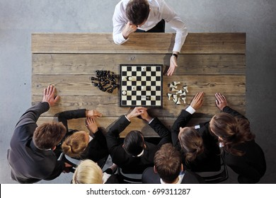 Business people playing chess, team of workers losing, leader is winning